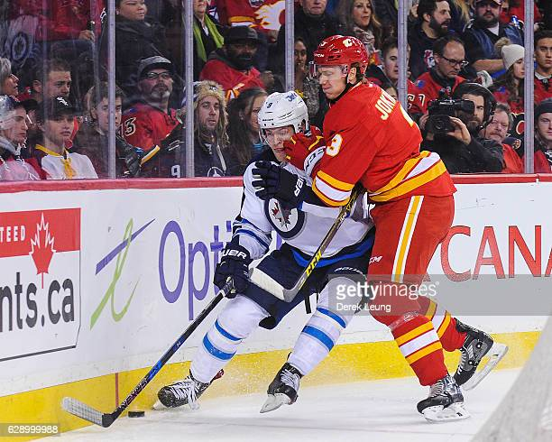 Jyrki Jokipakka of the Calgary Flames checks Andrew Copp of the Winnipeg Jets during an NHL game at Scotiabank Saddledome on December 10 2016 in...