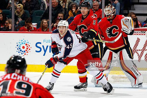 Jyrki Jokipakka of the Calgary Flames checks Lukas Sedlak of the Columbus Blue Jackets during an NHL game on December 16 2016 at the Scotiabank...