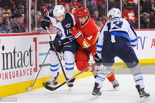 Jyrki Jokipakka of the Calgary Flames fights Adam Lowry of the Winnipeg Jets for the puck during an NHL game at Scotiabank Saddledome on December 10...
