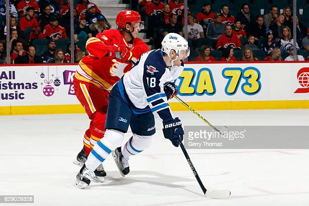 Jyrki Jokipakka of the Calgary Flames skates against Bryan Little of the Winnipeg Jets during an NHL game on December 10 2016 at the Scotiabank...