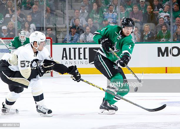 Jyrki Jokipakka of the Dallas Stars handles the puck against David Perron of the Pittsburgh Penguins at the American Airlines Center on October 8...