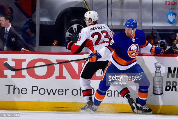 Jyrki Jokipakka of the Ottawa Senators and Jason Chimera of the New York Islanders battle along the boards during an NHL game at Barclays Center on...