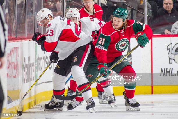Jyrki Jokipakka of the Ottawa Senators battles for the puck with Ryan White of the Minnesota Wild during the game on March 30 2017 at the Xcel Energy...