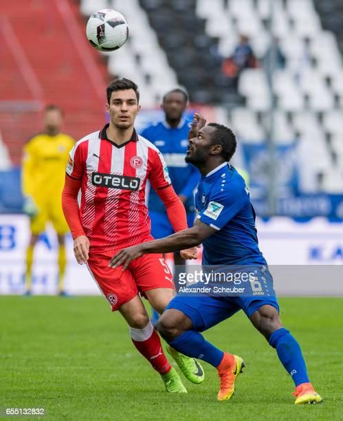 Kaan Ayhan of Fortuna Duesseldorf challenges Franck Kom of Karlsruhe during the Second Bundesliga match between Karlsruher SC and Fortuna Duesseldorf...