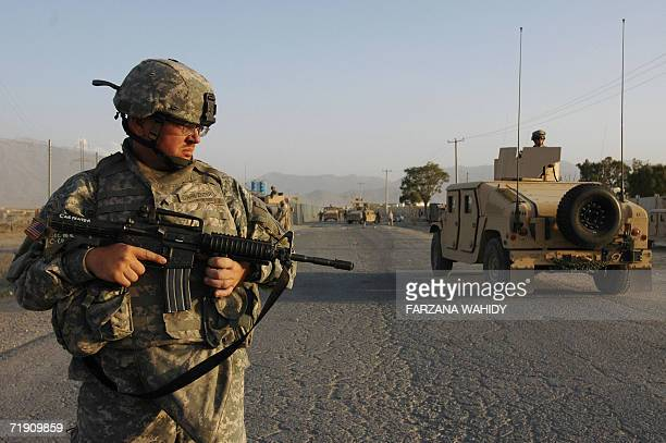 A US soldier stands guard near the site of a suicide bomb attack in Kabul 17 September 2006 A suicide attacker strapped with bombs jumped onto a...