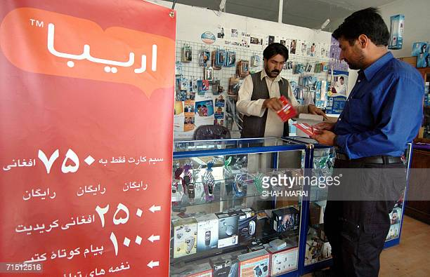 An Afghan man buys a SIM card for the country's third mobile phone operator Areeba Afghanistan in Kabul 25 July 2006 The company's entrance into the...