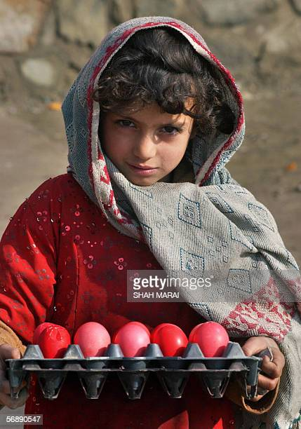 Young Afghan girl Shabbnam poses with a tray of eggs as she waits for customers on a street of Kabul 20 February 2006 Shabbnam earns approximately...