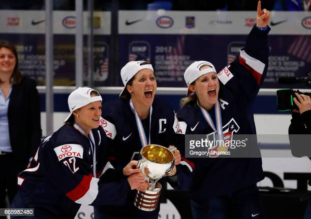 Kacey Bellamy Meghan Duggan and Monique Lamoureux of the United States react after receiving the championship trophy for beating Canada 32 in...