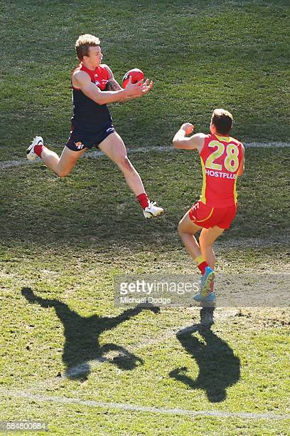Kade Kolodjashnij of the Suns collides into James Harmes of the Demons marks the ball during the round 19 AFL match between the Melbourne Demons and...