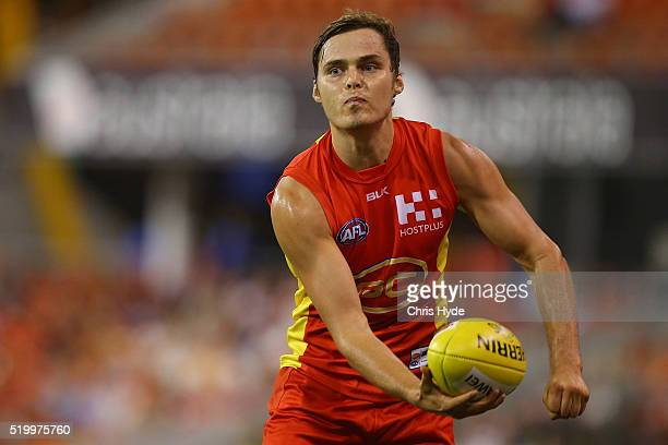 Kade Kolodjashnij of the Suns handballs during the round three AFL match between the Gold Coast Suns and the Carlton Blues at Metricon Stadium on...