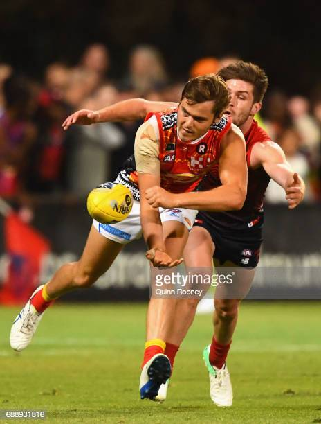 Kade Kolodjashnij of the Suns handballs whilst being tackled by Tomas Bugg of the Demons during the round ten AFL match between the Melbourne Demons...