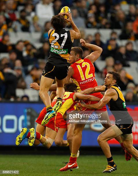 Kade Kolodjashnij of the Suns is knocked out by Sam Lloyd of the Tigers marking attempt during the 2016 AFL Round 12 match between the Richmond...
