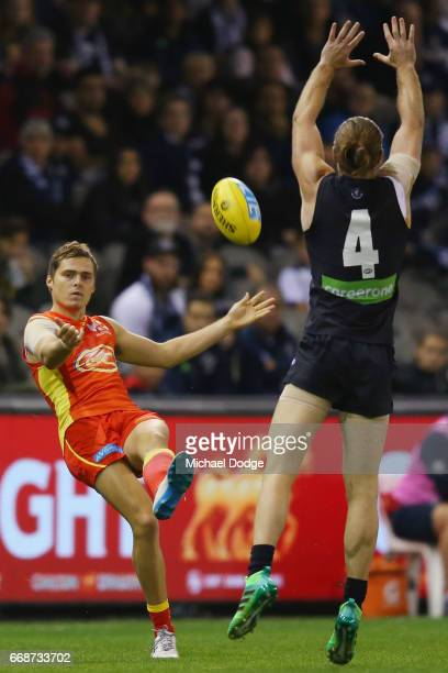 Kade Kolodjashnij of the Suns kicks the ball past Bryce Gibbs of the Blues during the round four AFL match between the Carlton Blues and the Gold...
