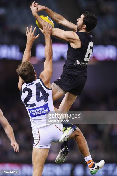 Kade Simpson of the Blues compete for the ball over Matt De Boer of the Giants during the round 12 AFL match between the Carlton Blues and the...