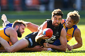Kade Simpson of the Blues handballs whilst being tackled by Mitchell Brown and Mark LeCras of the Eagles during the round 17 AFL match between the...