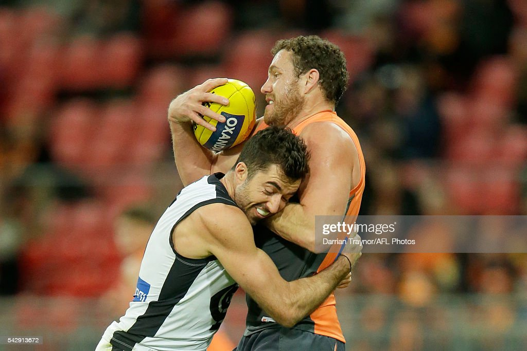 Kade Simpson of the Blues tackles Shane Mumford of the Giants during the round 14 AFL match between the Greater Western Sydney Giants and the Carlton Blues at Spotless Stadium on June 25, 2016 in Sydney, Australia.