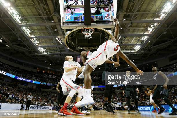 Kadeem Allen falls to the court as Lauri Markkanen of the Arizona Wildcats looks for a rebound against the Xavier Musketeers during the 2017 NCAA...