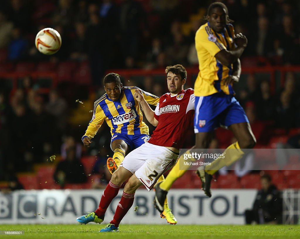 Kadeem Harris (L) of Brentford curls a shot past Brendan Moloney (C) of Bristol City during the Sky Bet League One match between Bristol City and Brentford at Ashton Gate on October 22, 2013 in Bristol, England.