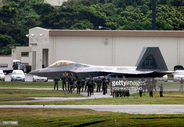 Military personnel gather arounf a new stealth fighter F22A Raptor at the Kadena Air Base in Kadena town southern island of Okinawa 17 February 2007...