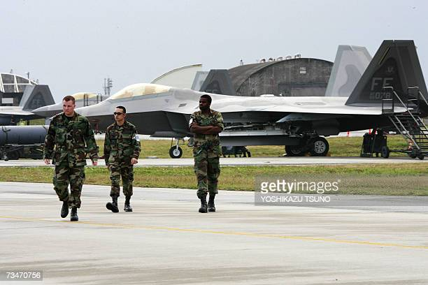 US military personnels walk by US Air Force's new stealth fighters F22A Raptor at the Kadena US Air Base in Kadena town southern island of Okinawa 18...