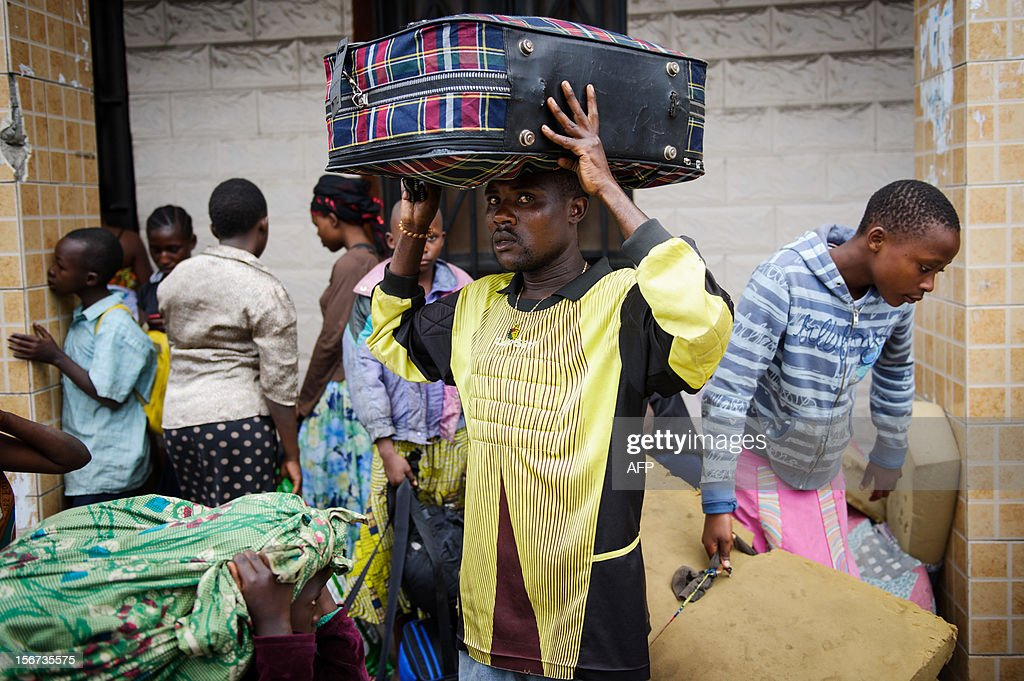 Kadogo Ombeni, 27, stands near the Rwandan border with Congo with a suitcase on his head after fleeing his home in the Bujovu Kabutembo district of Goma, in the east of the Democratic Republic of the Congo on November 20, 2012. Kadogo Ombeni said that government troops told residents of the area to 'evacuate' their homes last night, as the risk of an assault between M23 rebels and the army grew. 'If the authorities allow me to cross the border, I will. I don't have anywhere else to take refuge' he said. AFP PHOTO/PHIL MOORE