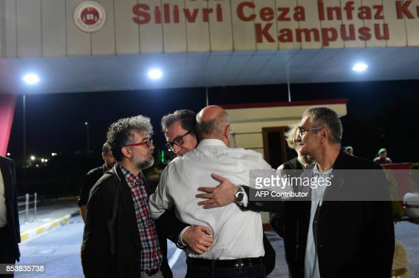 Kadri Gursel is welcomed by friends after his release from Silivri prison on September 26 2017 in Istanbul following a Turkish court order to free...