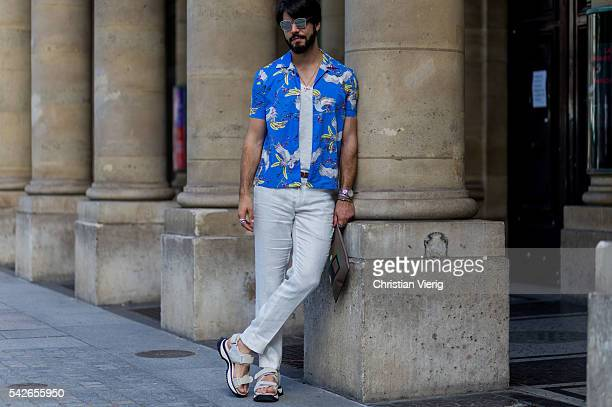 Kadu Dantas wearing a blue button shirt white pants and sandals outside Louis Vuitton during the Paris Fashion Week Menswear Spring/Summer 2017 on...