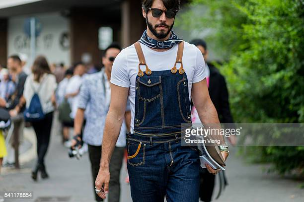 Kadu Dantas wearing a navy denim overall and white tshirt outside Versace during the Milan Men's Fashion Week Spring/Summer 2017 on June 18 2016 in...