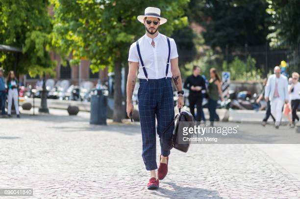 Kadu Dantas wearing white button shirt with short sleeves suspenders checked pants is seen during Pitti Immagine Uomo 92 at Fortezza Da Basso on June...