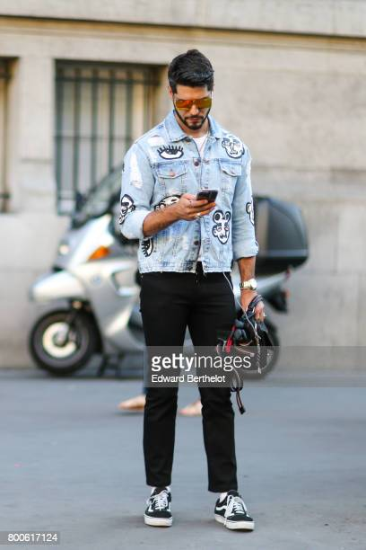 Kadu Dantas wears sunglasses a denim jacket with prints black pants sneakers a black leather bag outside the Hermes show during Paris Fashion Week...