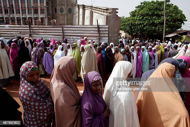 Female voters wait at a polling station in the Mando community as Africa's most populous nation prepares to vote in one of the closest elections...