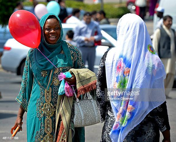 Kady Drame left exchanges greetings with another woman on Friday July 17 2015 as she joined thousands of Charlottearea Muslims gathered to mark the...