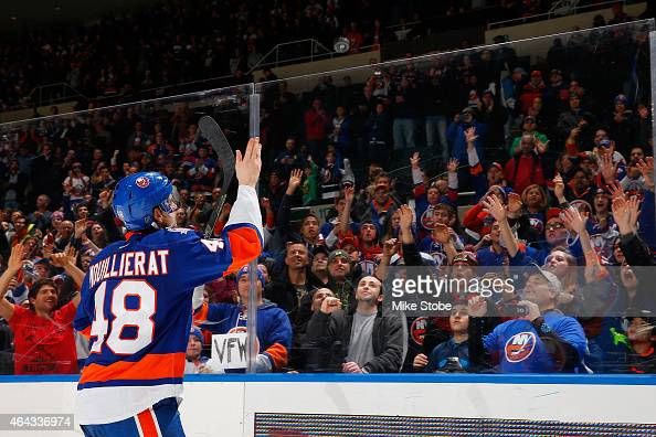 Kael Mouillierat of the New York Islanders tosses a puck to the fans after being named the second star of the game in which he scored his first...