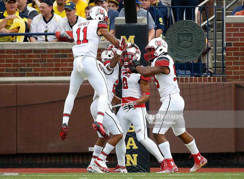 Kaelin Clay of the Utah Utes celebrates a second quarter touchdown with Troy McCormickSharrieff Shah Jr #59 and Davion Orphey while playing the...