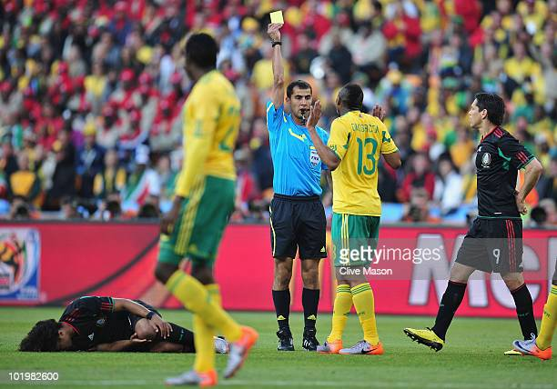 Kagisho Dikgacoi of South Africa is shown a yellow card by referee Ravshan Irmatov during the 2010 FIFA World Cup South Africa Group A match between...