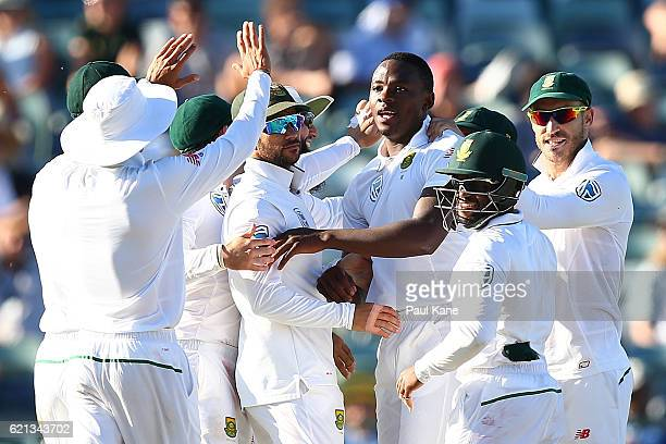 Kagiso Rabada of South Africa celebrates with team mates after dismissing Adam Voges of Australia during day four of the First Test match between...