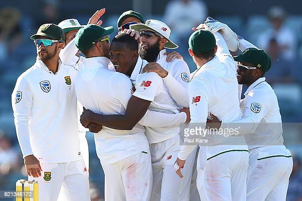 Kagiso Rabada of South Africa celebrates with team mates after dismissing Steve Smith of Australia during day four of the First Test match between...