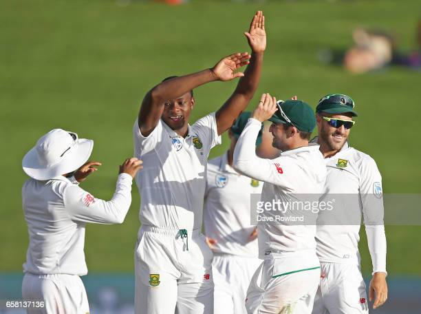 Kagiso Rabada of South Africa is congratulated on taking the wicket of Henry Nicholls of New Zealand during day three of the Test match between New...
