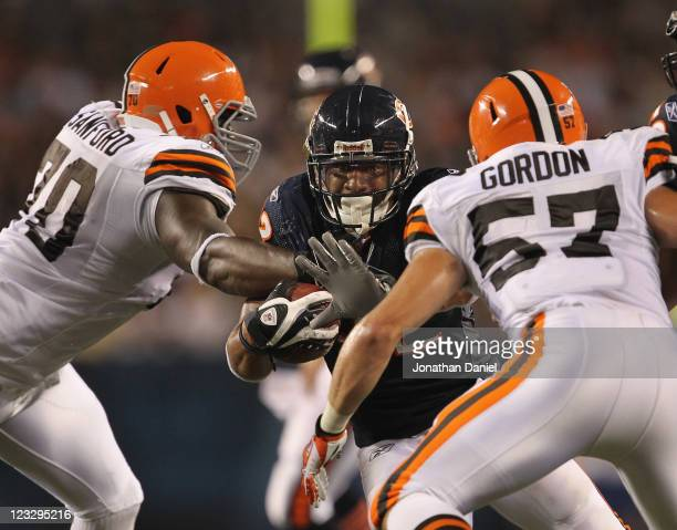 Kahlil Bell of the Chicago Bears runs against Brian Sanford and Eric Gordon of the Cleveland Browns during a preseason game at Soldier Field on...