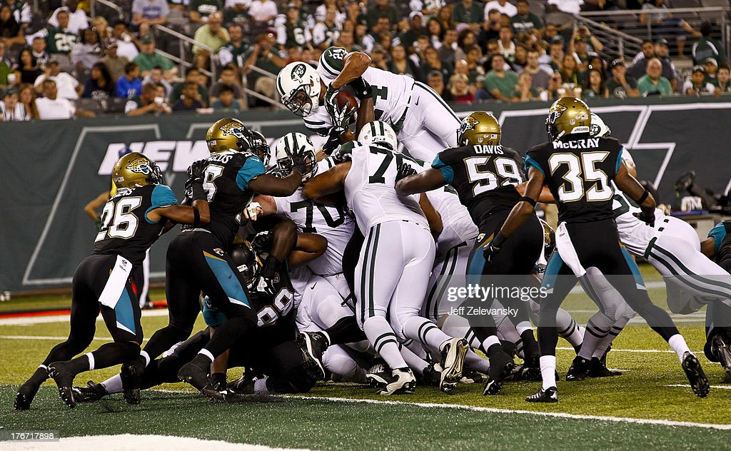 Kahlil Bell #24 of the NEw York Jets jumps over the line Jacksonville Jaguars during their preseason game at MetLife Stadium on August 17, 2013 in East Rutherford, New Jersey.