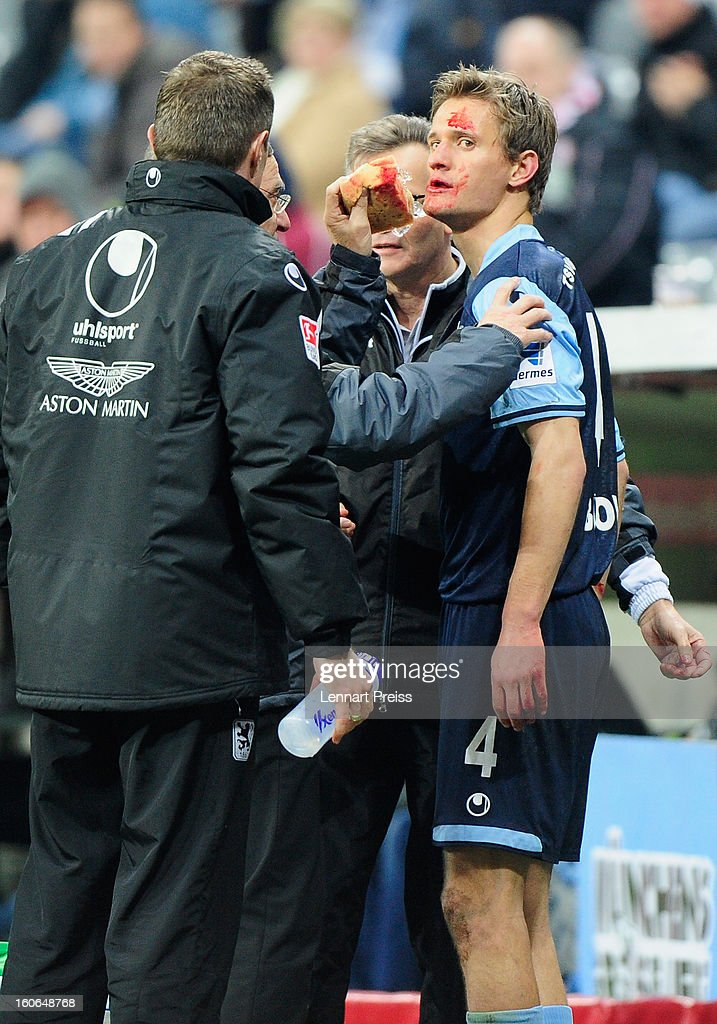 Kai Buelow (R) of Muenchen receives medial treatment after an injury during the Second Bundesliga match between TSV 1860 Muenchen and 1. FC Kaiserslautern at Allianz Arena on February 4, 2013 in Munich, Germany.