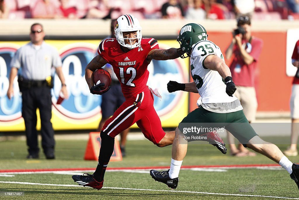 Kai De La Cruz #12 of the Louisville Cardinals catches a 30-yard touchdown pass in the fourth quarter of the game against Nathan Carpenter #35 of the Ohio Bobcats at Papa John's Cardinal Stadium on September 1, 2013 in Louisville, Kentucky.