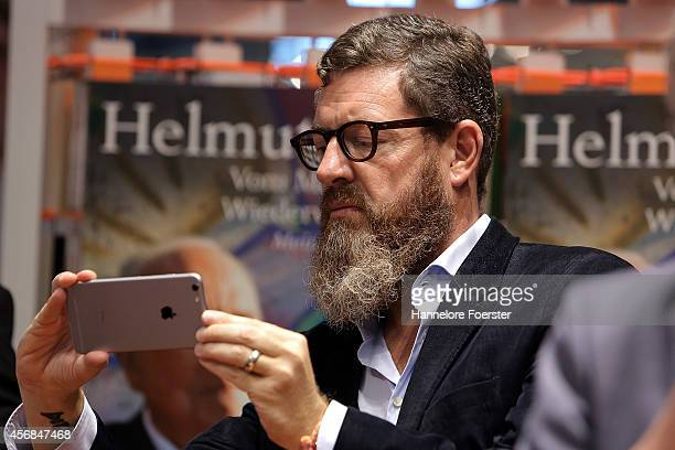 Kai Diekmann chief editor of 'Welt' takes pictures during the presentation of the Helmut Kohl book at the Droemer Knaur Verlag stand at the 2014...