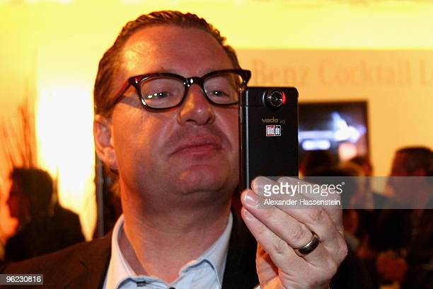 Kai Diekmann EditorinChief BILD takes photos with his mobile during the Burda DLD Nightcap 2010 at the Bellvedere Hotel on January 27 2010 in Davos...