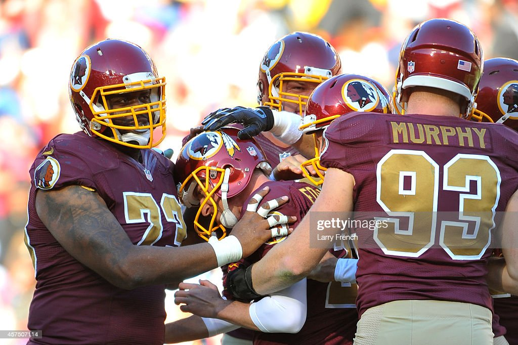Kai Forbath #2 of the Washington Redskins is congratulated by teammates after kicking the game winning field goal against the Tennessee Titans at FedEx Field on October 19, 2014 in Landover, Maryland.