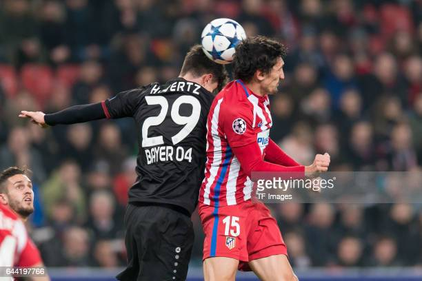 Kai Havertz of Bayer Leverkusen and Stefan Savic of Atletico Madrid battle for the ball during the UEFA Champions League Round of 16 first leg match...