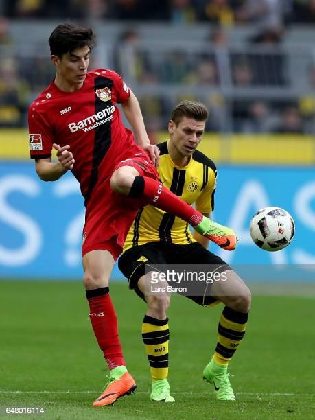 Kai Havertz of Bayer Leverkusen is challenged by Lukasz Piszczek of Dortmund during the Bundesliga match between Borussia Dortmund and Bayer 04...