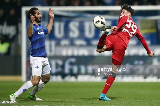 Kai Havertz of Leverkusen is challenged by Hamit Altintop of Darmstadt during the Bundesliga match between SV Darmstadt 98 and Bayer 04 Leverkusen at...