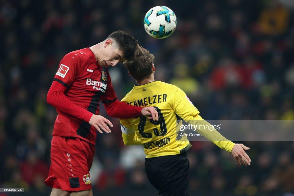 Kai Havertz of Leverkusen jumps for a header with Marcel Schmelzer of Dortmund and hits the cross bar during the Bundesliga match between Bayer 04 Leverkusen and Borussia Dortmund at BayArena on December 2, 2017 in Leverkusen, Germany.