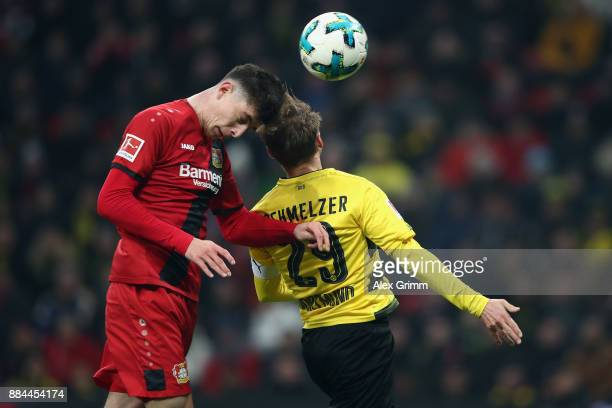 Kai Havertz of Leverkusen jumps for a header with Marcel Schmelzer of Dortmund and hits the cross bar during the Bundesliga match between Bayer 04...